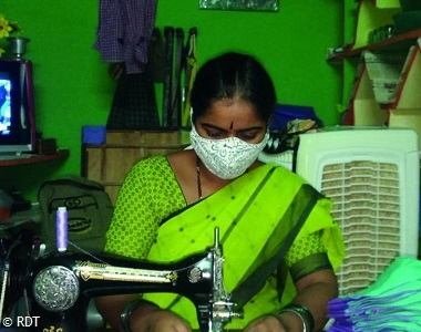 Corona-Hilfe Indien, Frau näht Maske, um Geld zu verdienen